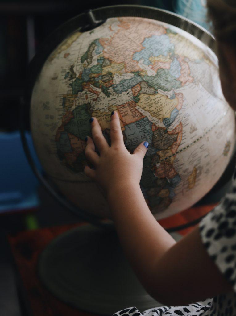 Child's hand on globe